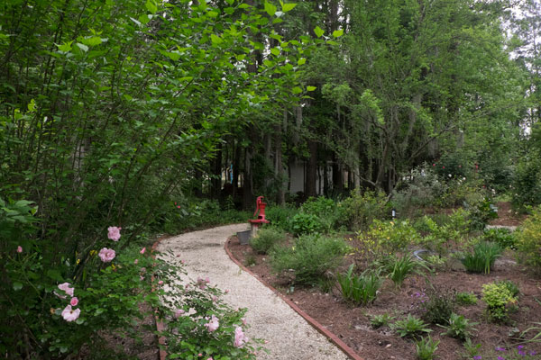 Garden Paths Wind Their Way Through Different Spaces. Keep An Eye Out For  The Bright Red Water Pump.